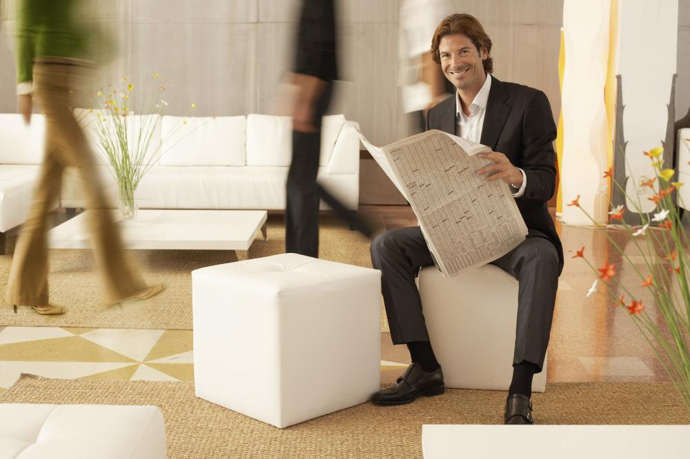 full-length-portrait-of-businessman-holding-newspaper-while-coworkers-walking-in-office